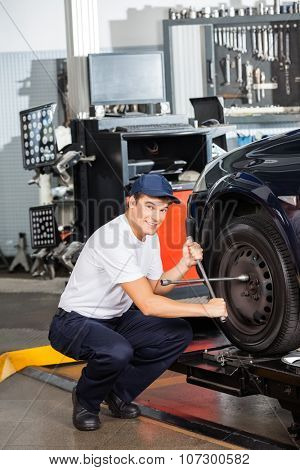 Portrait of smiling mechanic fixing car tire at garage
