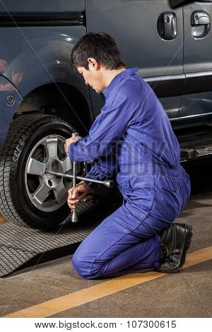 Side view of male mechanic fixing car tire at auto repair shop