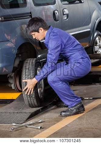Side view of male mechanic changing car tire at auto repair shop