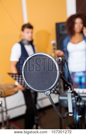 Closeup of condenser with band members in background at recording studio