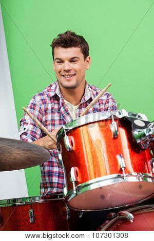 Smiling young man playing drums in recording studio