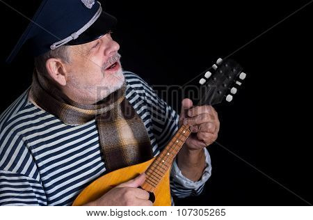 Senior man in striped vest and comforter with mandolin