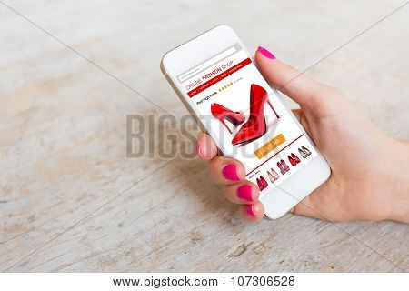 Woman using smartphone to buy shoes online