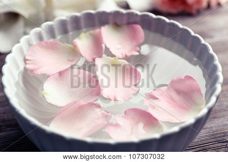 Tender pink rose petals in a bowl of water on wooden background