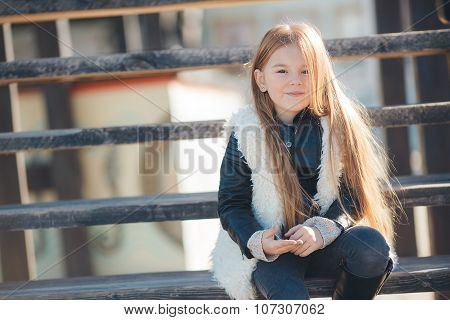 Little girl sitting on the steps near the house
