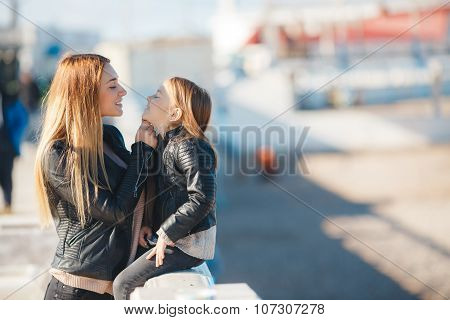 Mom and daughter spend time walking near the sea