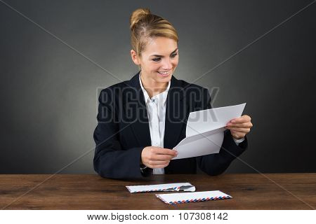 Young Businesswoman Reading Letter At Desk