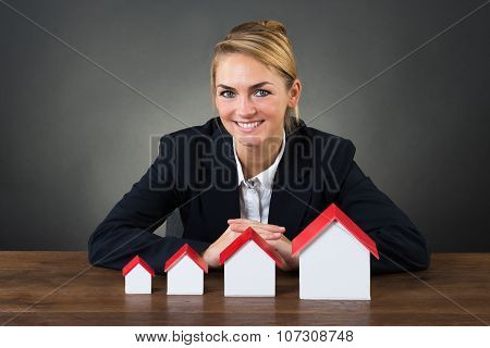 Smiling Businesswoman With Model Houses Arranged In Graph Order