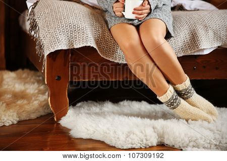 Legs of woman in warm socks on white carpet on wooden  bed background