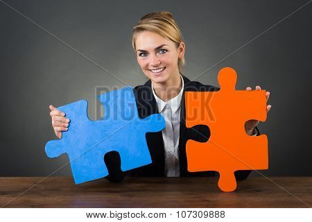 Businesswoman Holding Puzzle Pieces At Desk