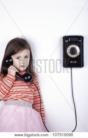 Serious sad child talking on phone, white background