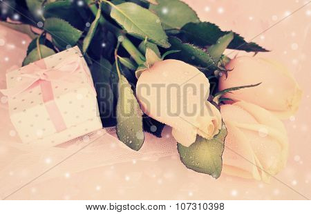 Beautiful roses and gift box on pink cloth background