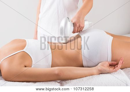 Midsection Of Beautician Using Laser Machine On Customer's Back
