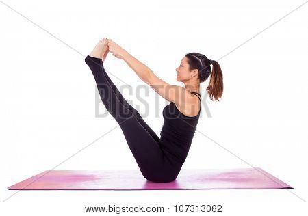 Beautiful woman doing Navasana  pose on yoga class. Studio shot.