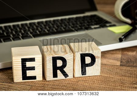ERP (Enterprise Resource Planning) written on a wooden cube in a office desk