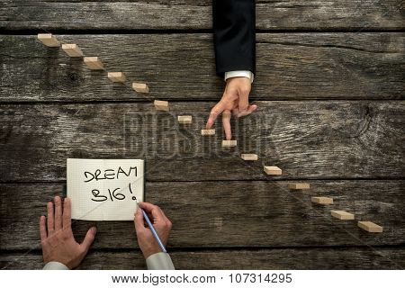 Male Hand Writing An Encouraging Message Dream Big In A Notepad As A Businessman Walks His Fingers U