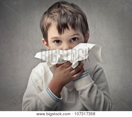 A young boy with a tissue to his nose