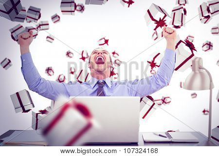Successful businessman with hands raised sitting at desk against white and red gift box