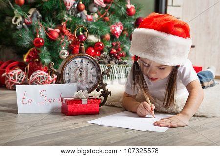 Pensive Girl In Santa Hat Writes Letter To Santa