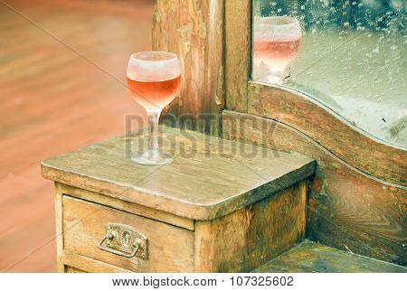 Glass Of Rose Wine Left On An Old Dresser In A Rural House