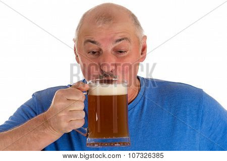 gray haired man drinking beer from a mug