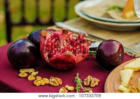 Sliced Pomegranate With Plums On A Maroon Table.