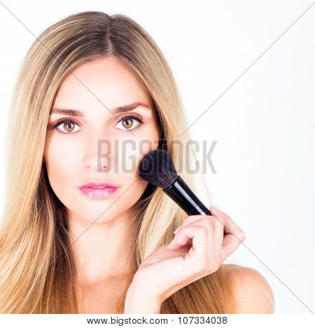 Woman with make-up and brush for rouge. Close up.