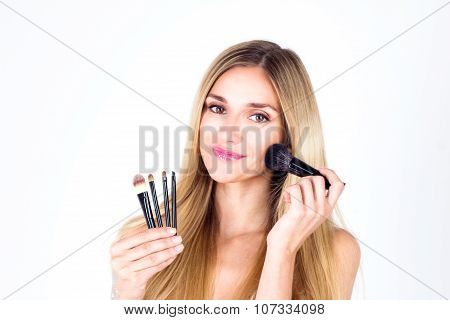 Happy beautiful woman apply blush on face with smile. Make-up artist.