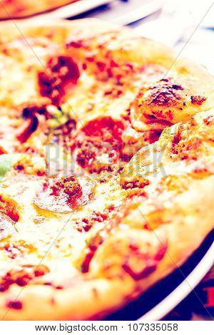 Fresh combo pizza in Italian restaurant on table.