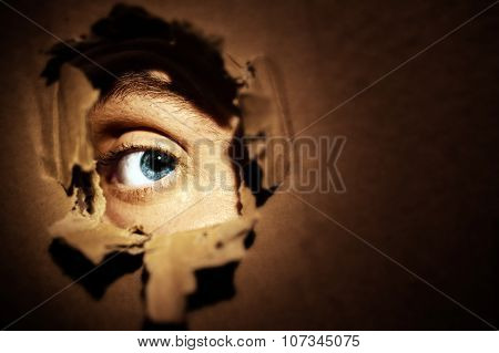Male eyes spying through a hole in the wall