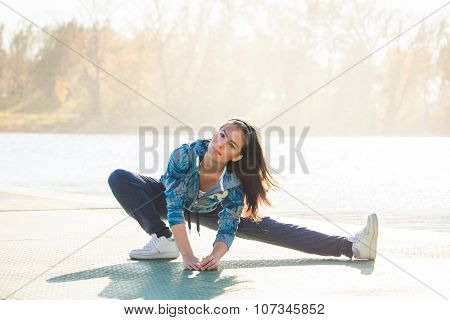 young woman in tracksuit exercise on pontoon at lake,  sunny autumn day, full body shot,