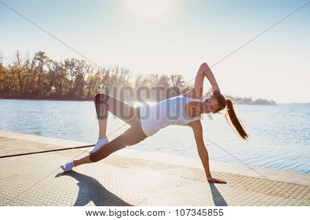 young woman in leggings and white undershirt   on pontoon at lake practice yoga, sunny autumn day