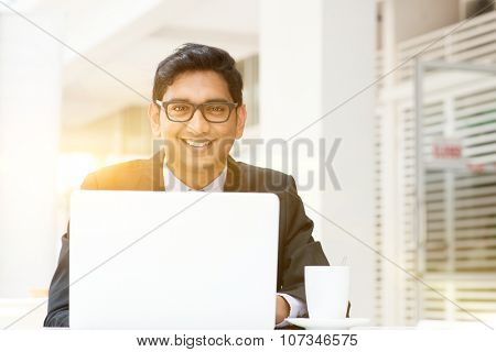 Asian Indian business people using a laptop or notebook computer at cafe, with a cup of coffee. India male business man, modern building with beautiful golden sunlight as background.