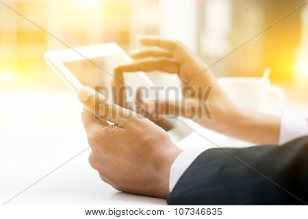 Close-up of Indian male hands touching digital tablet, formal businessman with cup of coffee on table, focus on hand with bokeh and light.
