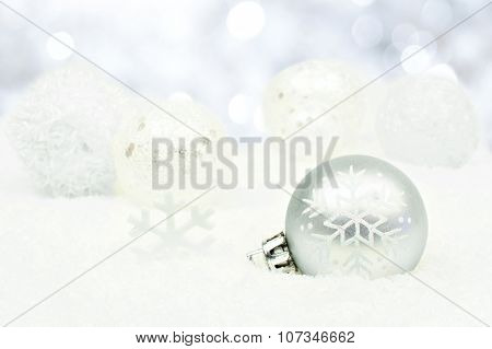 Silver Christmas ornaments in snow with twinkling background