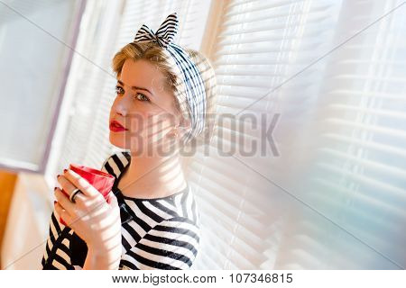 Elegant pinup girl holding cup of drink