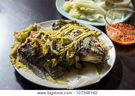 Steamed Tilapia With Vegetable And Chili Sauce On Black Wooden Table