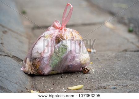 Garbage held in a polymer bag being thrown to the street in an Asia city