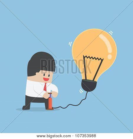 Businessman Pumping Air Into Idea Balloon