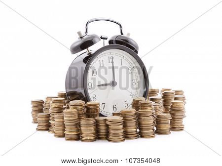 Time is money. Alarm clock with stacks of coins. Clipping path included.