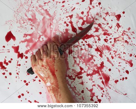 Conceptual Image Of A Victim Hand Holding A Sharp Knife With Blood On It Resting On A Concrete Floor