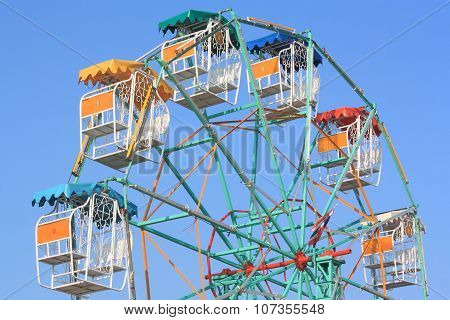 Colorful Ferris wheel with blue sky in amusement park.