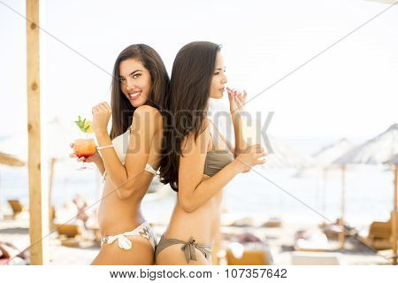 Pretty Young Women With Coctails On The Beach