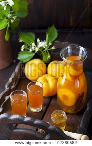 Apricot and cinnamon homemade liquor with fresh flowers