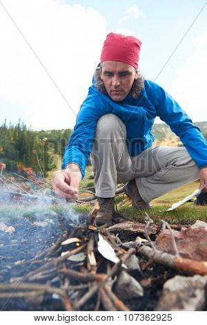 hiking adventure, hiking man try to light fire,  collecting woods for fire