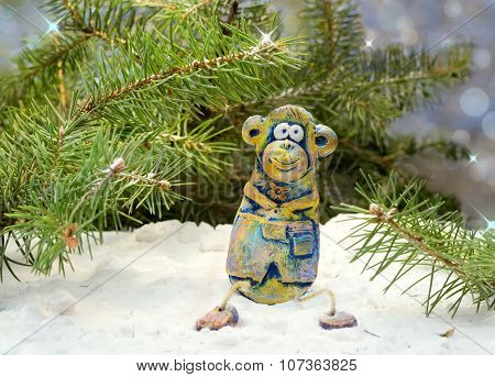 merry monkey from clay pottery sits under the tree in the snow