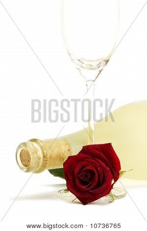wet red rose with a dull prosecco bottle and a empty champagne glass