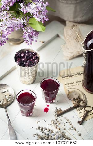 Blackcurrant homemade liquor with lilac flowers. Wooden background