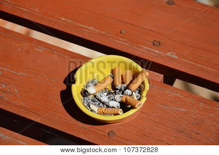 yellow ashtray and cigarette filter on wood board