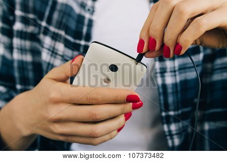 Woman In Plaid Shirt And Red Manicure Connect Headphones To The White Mobile Phone Close-up